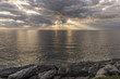 Sun rays shining through clouds over the ocean