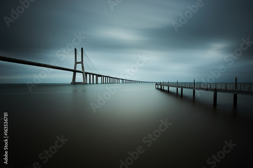 Poster vasco da gama bridge in lisbon on a cloudy day