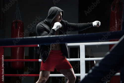 Boxer man workout in boxing ring. Boxing fighter in hoodie