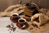 Coffee cup and old vintage coffee grinder over wooden background with sackcloth