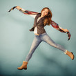 Woman fashion autumn girl jumping, flying in air on blue