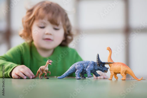toddler kid playing with a toy dinosaur Poster