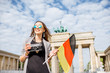 Portrait of a young smiling woman tourist standing with german flag in front of the famous Brandenburg gates in Berlin