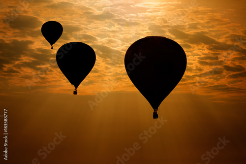 Hot air balloons silhouette against morning sky