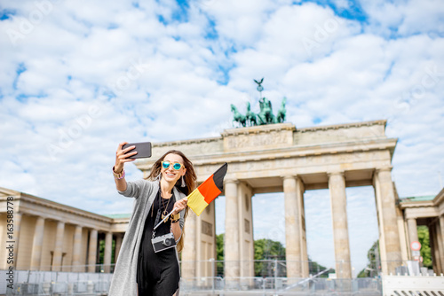 Young woman tourist making selfie photo with german flag standing in front of th Poster