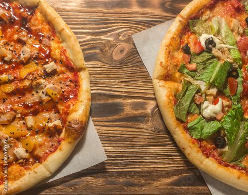 Две пиццы на деревянном фоне