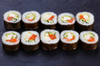 Appetizing fresh maki sushi roll with salmon and tofu cheese served on black slate, close up. Japanese healthy seafood.