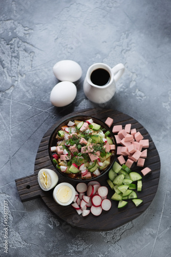 Black wooden serving board with okroshka or cold soup with kvass, vertical shot on a grey stone background, high angle view