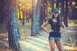 athletic woman listening music on a running in forest - 163628308