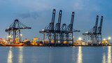 Container Cargo freight ship with working crane bridge in shipyard at dusk for Logistic Import Export background.  Industry Concept - 163628747