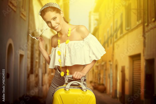 Elegant woman with a suitcase travel and umbrella on street of italian city Poster