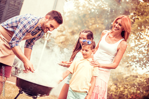 Happy family having a barbecue in their garden