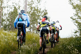 group of athletes mountain biking on forest trail