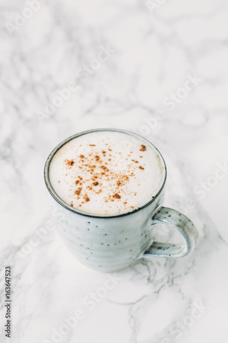 Cappuccino in a rustic style mug on a marble table