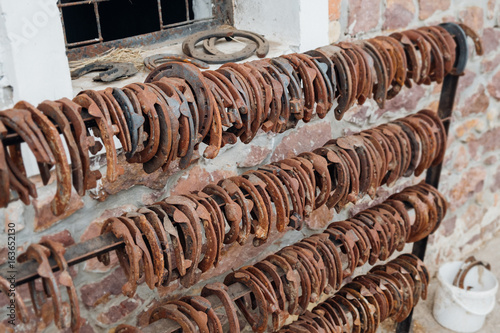 Rack of horse shoes outside the stables waiting to be used. Poster