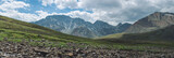 Panorama of mountains covered with green and blue sky with clouds. View of the valley - 163652739