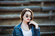 Outdoor fashion closeup portrait of young pretty woman in summer sunny day on street