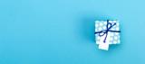 Little handmade present box on a blue background - 163654343