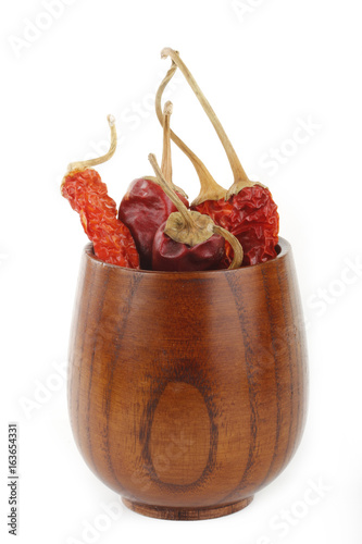 dried red chili pepper in wooden cup isolated