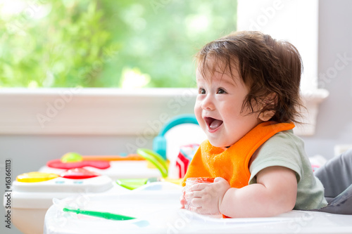 Happy little baby boy with a big smile eating food