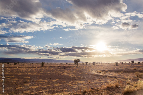 Sunset over desert in Morocco with cloudy sky