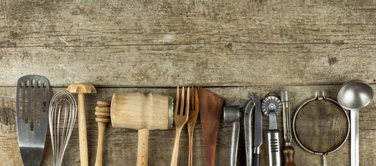 Kitchen tools on a wooden table. Cook's tools. Traditional equipment of rural cuisine. © martinfredy