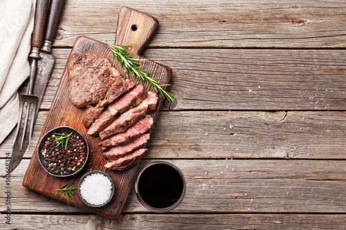 Grilled beef steak with spices on cutting board - 163668324