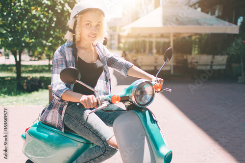 Foto op Canvas Scooter Young cheerful girl driving scooter in in city. Portrait of a young and stylish woman with a moped.