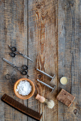 Barbershop. Men's shaving and haircut. Brush, razor, foam, sciccors on wooden table background top view copyspace