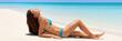 Bikini body sexy woman sunbathing on beach banner. Luxury travel girl tanning relaxing lying down on white sand tropical getaway in swimsuit suntan.