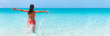 Summer fun beach woman splashing water with open arms banner. Panorama landscape of tropical ocean on travel holiday. Bikini girl running in freedom and joy with hands up enjoying the sun.
