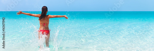 Leinwanddruck Bild Summer fun beach woman splashing water with open arms banner. Panorama landscape of tropical ocean on travel holiday. Bikini girl running in freedom and joy with hands up enjoying the sun.