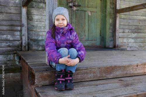Девочка сидит на крыльце старого дома Poster