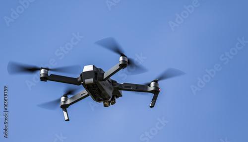 SWINDON, UK - JULY 9, 2017: Drone in Flight over a blue sky background