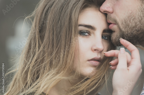 male lips touching adorable face of pretty girl