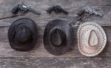Three cowboy hats and three revolvers - 163700792