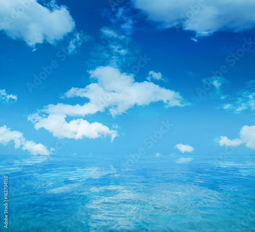 Infinite water surface over blue sky background