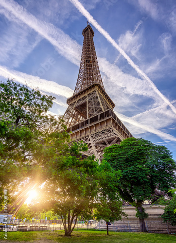 Paris Eiffel Tower and Champ de Mars in Paris, France. Eiffel Tower is one of the most iconic landmarks in Paris. The Champ de Mars is a large public park in Paris.