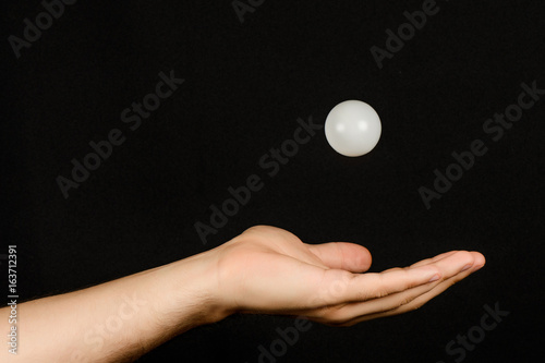 Plexiglas Men's hand which catches the white plastic ball isolated on black background