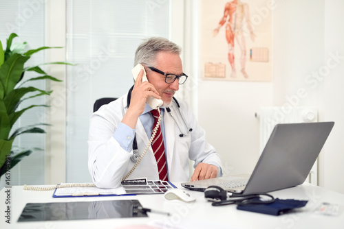Doctor talking on the phone in his studio - 163714921