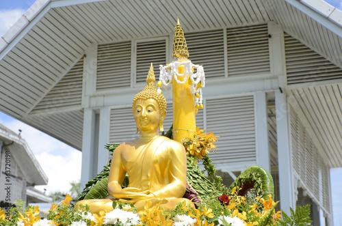 Buddha statue on bright sky background.