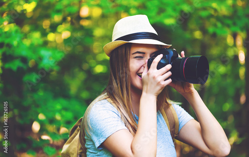 Female photographer in the forest with a camera - 163726505