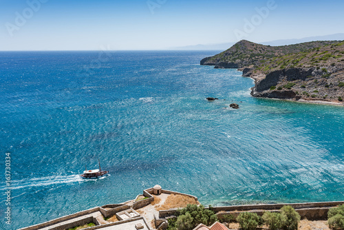 Top of Spinalonga. Picturesque view to the blue sea and island with mountain.