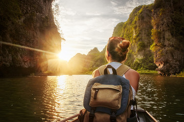 Woman traveling by boat enjoying sunset among of karst mountains