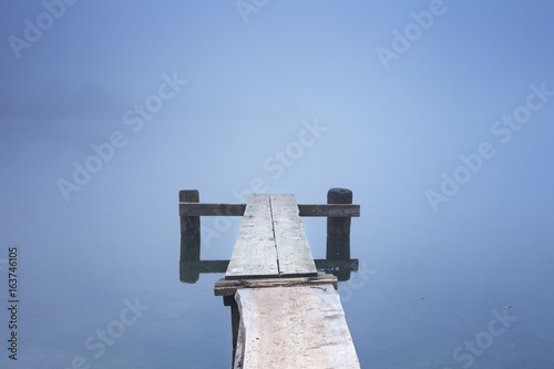 Plexiglas Pier Jetty on Bohinj Lake in Slovenia on a misty morning