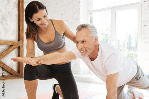 Positive delighted man doing exercises with pleasure - 163749173