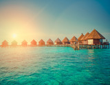 houses over the transparent quiet sea water  on a sunset , toning. Maldives - 163749563