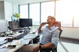 Business investor in a happy mood talking over phone in office. - 163751382