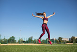 Young happy sportswoman in sportswear jumping and flying on stadium green grass outdoors. She enjoying summer. Healthy lifestyle concept, sport activity.