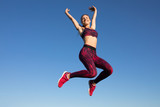 Isolated of young happy sportswoman in sportswear jumping and flying at blue sky background. She enjoying summer. Healthy lifestyle concept, sport activity.